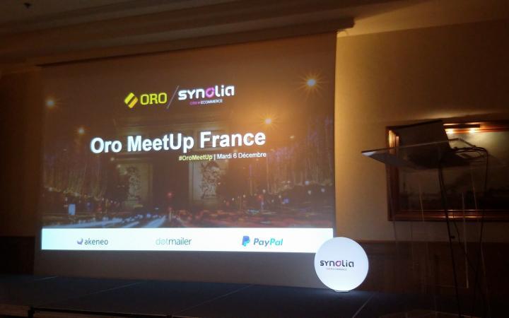 Het podium tijdens de Oro Meetup in Frankrijk. Op het podium hangt een scherm waar de eerste slide van een presentatie te zien is.
