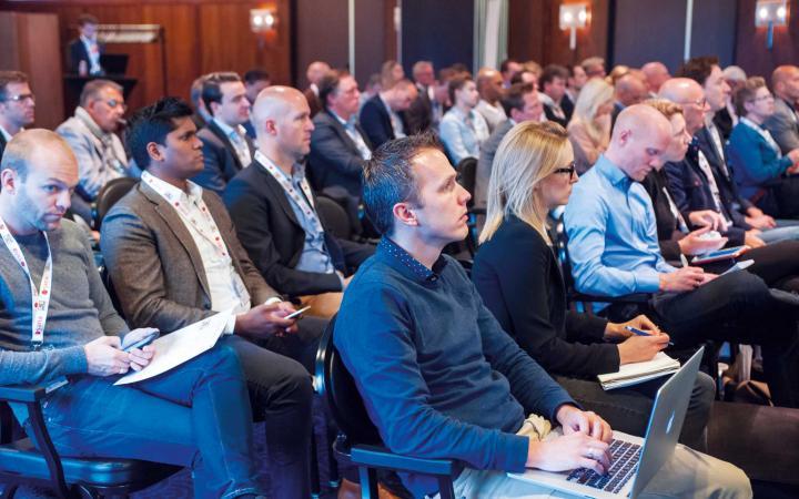 Publiek van circa 50 mensen tijdens een conferentie. Een groot deel van het publiek is aantekeningen aan het maken.