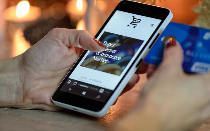 Een mobiele telefoon in de handen van een vrouw. Op de telefoon is een webshop geopend.
