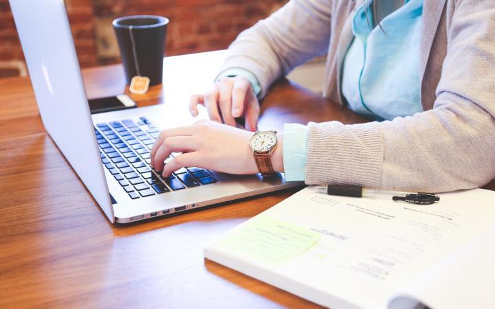 Een persoon die op een laptop aan het werken is.