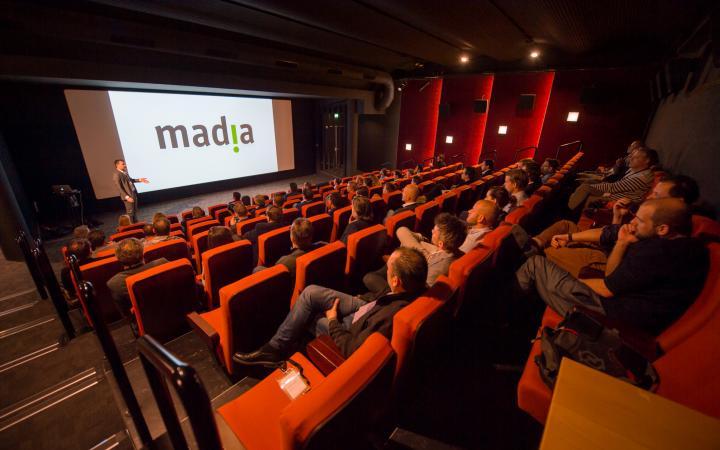 Een bioscoopzaal vol mensen met op het scherm het logo van Madia